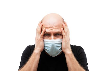 Human population virus, infection, flu disease prevention and industrial exhaust emissions protection concept - young adult bald head man wearing respiratory protective medical mask suffers headache Stockfoto