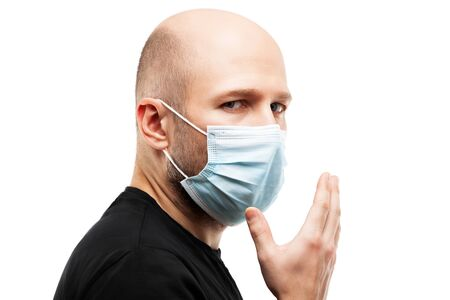 Human population virus, infection, flu disease prevention and industrial exhaust emissions protection concept - young adult bald head man wearing respiratory protective medical mask hand hiding face Stockfoto - 143237061
