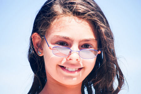 shrewd: intellettual child in a classic model pose with her lenses