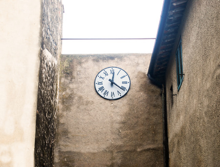 corner clock: ancient clock in tuscany medieval country place Stock Photo