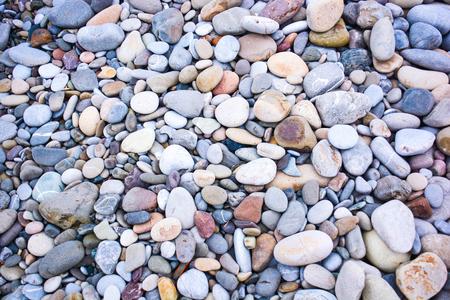 Antecedentes de las piedras del mar en un plan uniforme Foto de archivo - 50055023