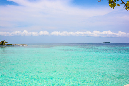 atoll of the tropics and maldives that are reflected in a sea of emerald with a cobalt blue sky