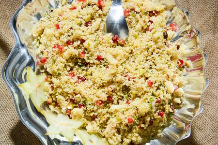 Italian couscous with pomegranate corn pistachios and thinly sliced vegetables
