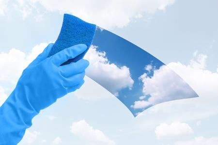 gant blanc: Main dans la fen�tre avec bleu �ponge de nettoyage des gants  Banque d'images