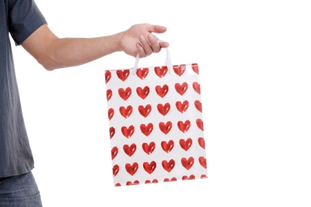 Mans hand holding valentines paper bag on a white background