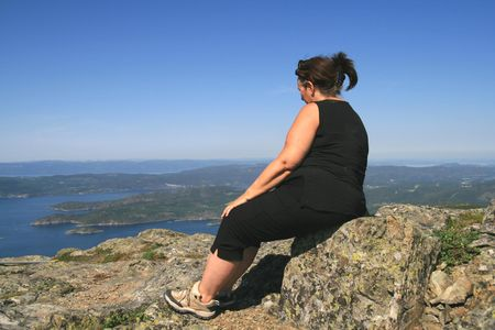 midlife: Overweight woman on a mountain top