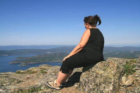 donne obese: Sovrappeso donna su una cima di montagna