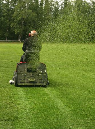 Caretaker on a tractor mowing a soccer field Stock Photo