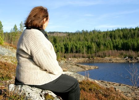 Overweight woman by a lake Stock Photo