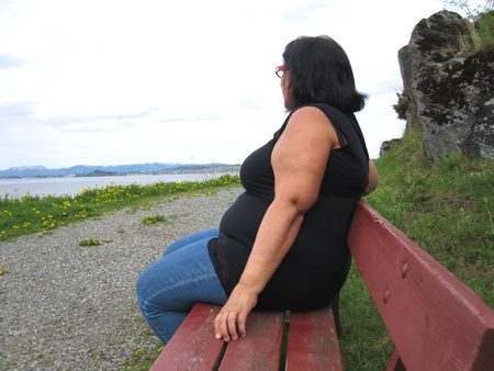 menopause: Obese woman alone on a bench