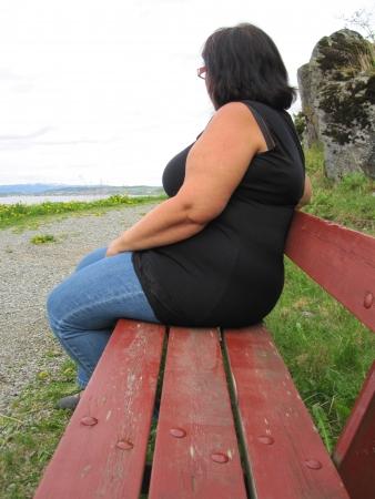 donne obese: Donna obesa da solo su una panchina Archivio Fotografico