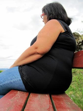 mujer gorda: Obesa mujer sola en un Banco