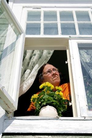Elderly woman in an open window Stock Photo - 13171340