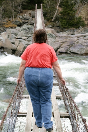 large woman: Obese woman on a suspension bridge