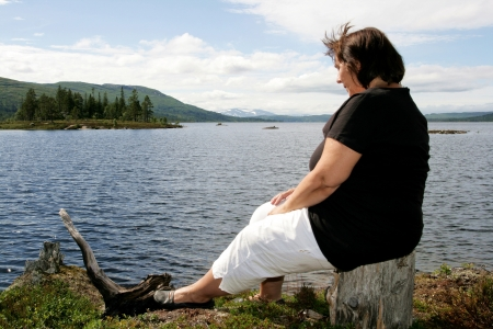 Obese woman sitting by a lake photo