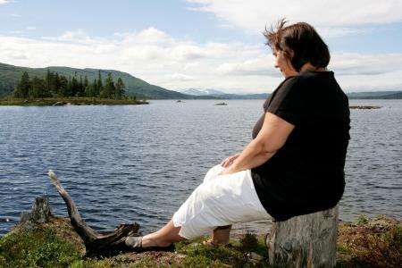 Obese woman sitting by a lake photo