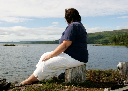 sobre peso: Mujer obesa sentada junto a un lago Foto de archivo
