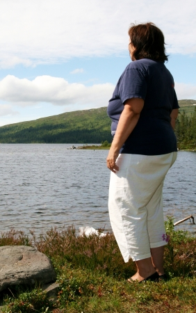 Obese woman standing by a lake