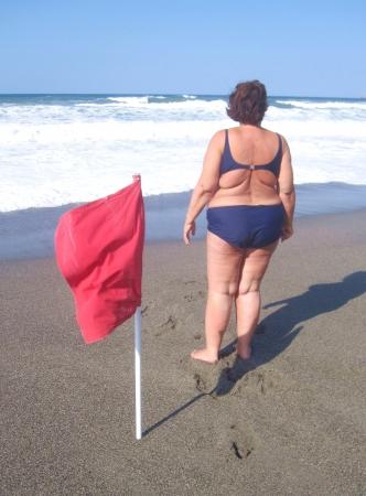 Mujer obesa en bikini en una playa con bandera roja Foto de archivo - 15152785