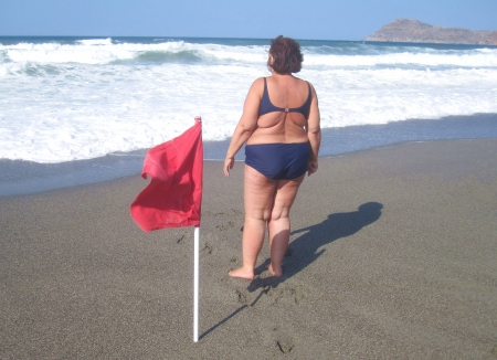 warning back: Obese woman in bikini on a beach with red flag Stock Photo