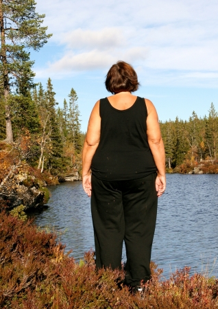 Obese woman standing by a tarn Stock Photo
