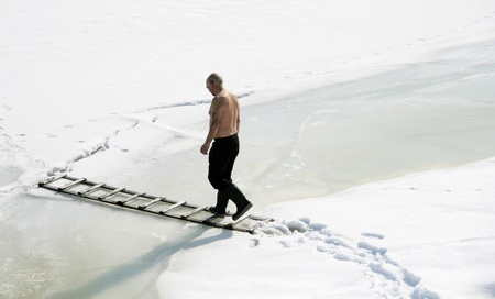 ice dam: Man walking on a ladder on a frozen lake Stock Photo