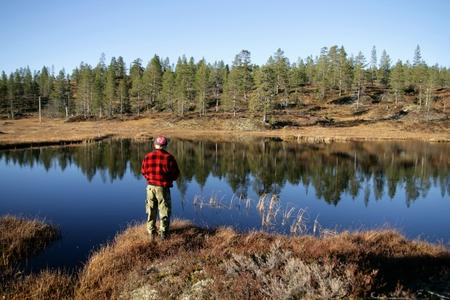 late sixties: Man fishing by a reflective tarn Stock Photo