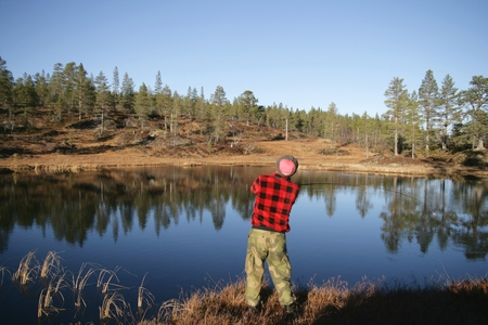 Man fishing by a reflective tarn Stock Photo