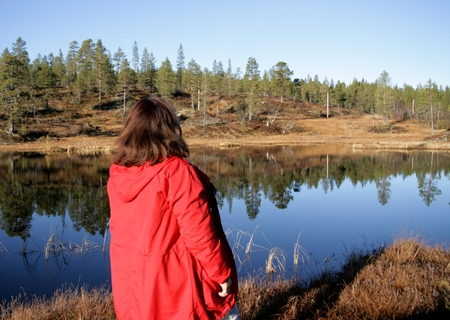 late fall: Woman standing by a reflective tarn in late fall Stock Photo