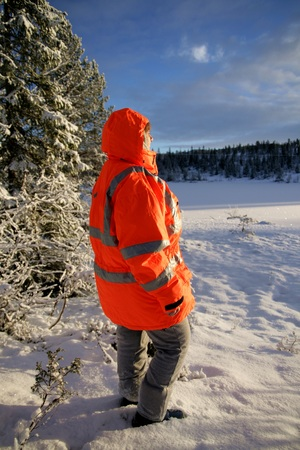frozen lake: Woman in rescue crew jacket standing by a frozen lake