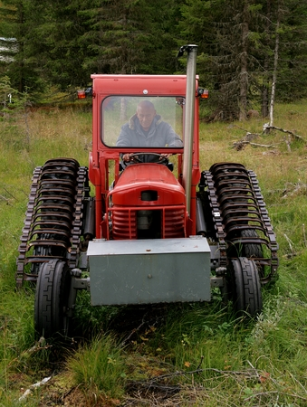 Man trying to start an old red tractor