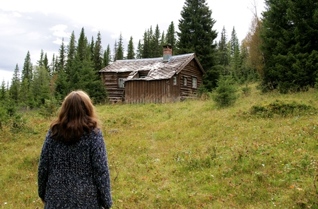 Woman looking up at an old cottage