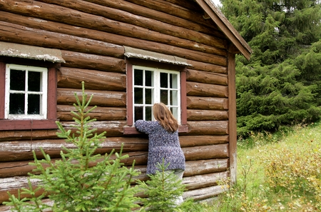 Woman outside an old cottage looking in through a window