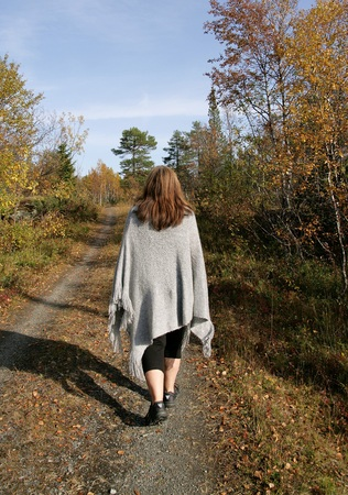 Woman walking on a dirt road in an autumn forest Stock Photo