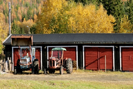 Two old tractors by a garage