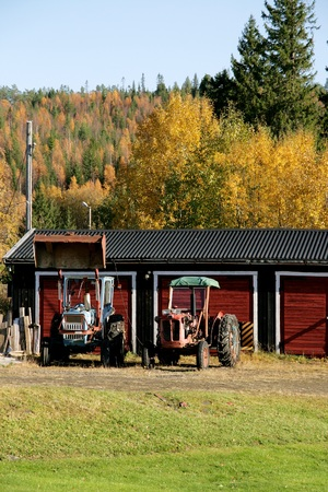 Two old tractors parked outside a garage