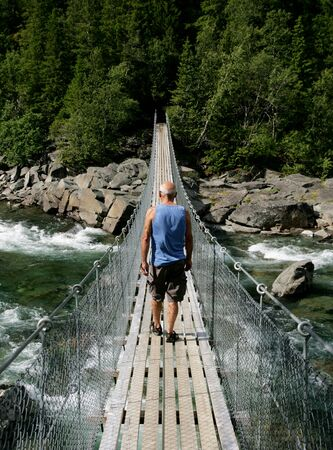 Man walking on a suspension bridge over a waterfall