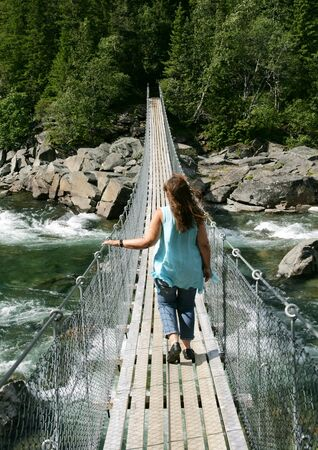 Woman walking on a suspension bridge over a waterfall in summer
