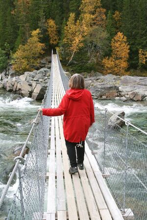 Woman walking on a suspension bridge over a steam