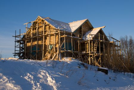 costruction: Costruction of new wood house. Sun, snow, winter.