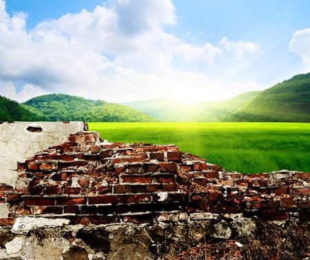 muro rotto: muro danneggiato e paesaggio perfetto  Archivio Fotografico