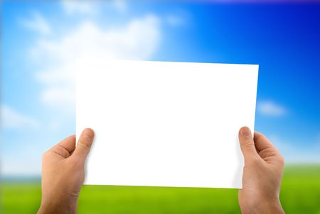 white paper in hand and green field Stock Photo
