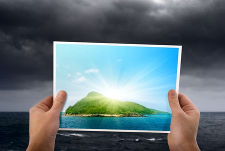 stormy weather and photo of tropical island in hands Stock Photo