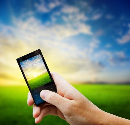 mobiele telefoon in de hand en land zonsondergang