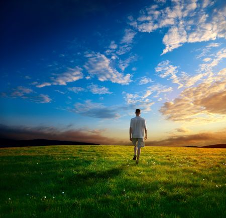 caminar: un hombre de la primavera y el campo de hierba y la puesta de sol Foto de archivo