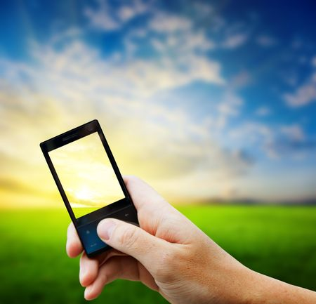 cell phone in hand and country sunset Stock Photo - 5190986