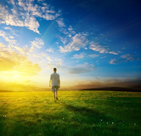 one man and field of spring grass and sunset photo
