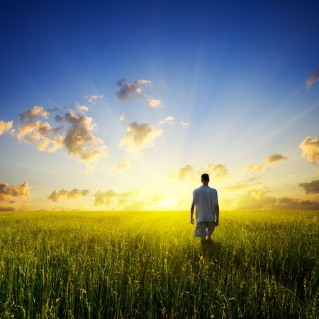walking young man over field and sunset Stock Photo