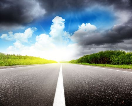 sulight: road black clouds and sun Stock Photo