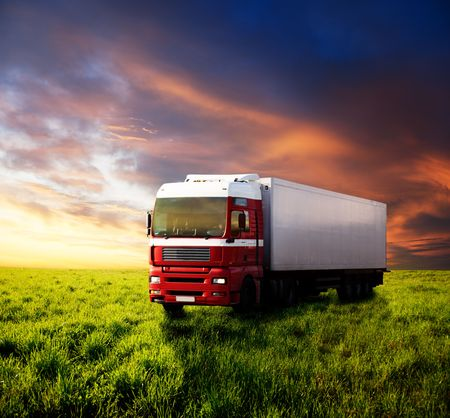 field of grass in sunset and truck photo